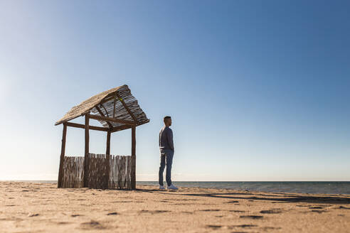 Man looking at sea view while standing on beach during sunny day - MIMFF00574