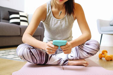 Woman using mobile phone while sitting on exercise mat at home - AODF00317