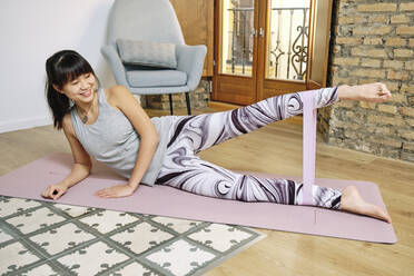 Smiling woman exercising with resistance band while lying on exercise mat at home - AODF00320