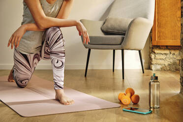 Young woman doing lunges while crouching on exercise mat at home - AODF00323