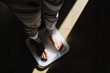 Young woman standing on weight scale in dark at home - AODF00326