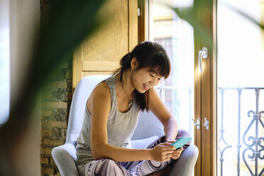Smiling woman using mobile phone while sitting on chair at home - AODF00335