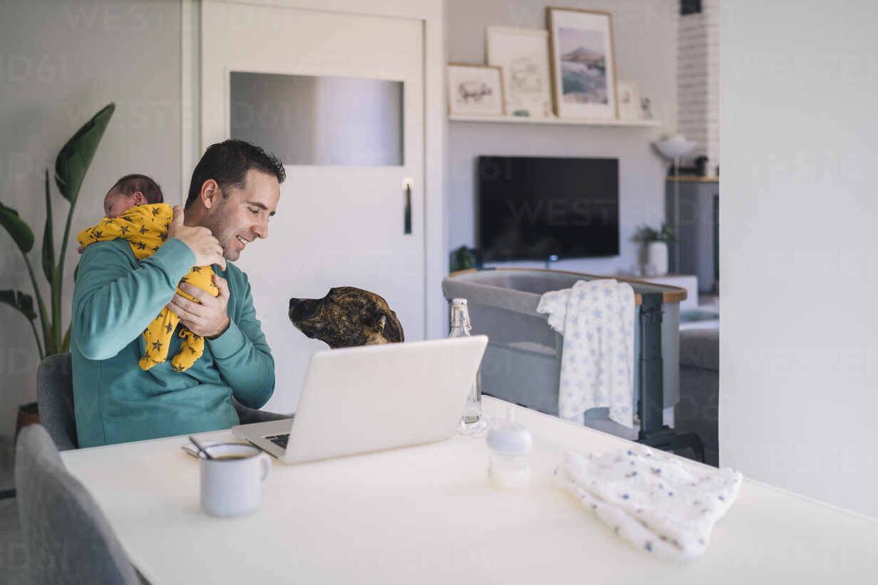 Father carrying son while looking at dog in home office - MPPF01534 - Manu Padilla Photo/Westend61