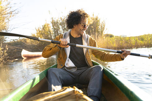 Smiling man wearing sunglasses paddling through oar while sitting in canoe on river - SBOF02677