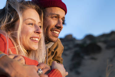 Portrait of smiling young couple in the dunes at sunset and cuddling - SBOF02680