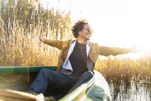 Carefree man with arms outstretched smiling while sitting in canoe on river - SBOF02683