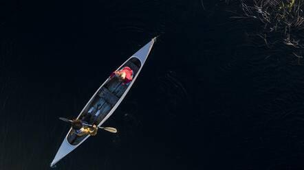 Couple paddling in canoe on river - SBOF02686