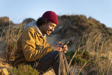 Portrait of young man sitting in the dunes at sunset looking at his smartphone - SBOF02689