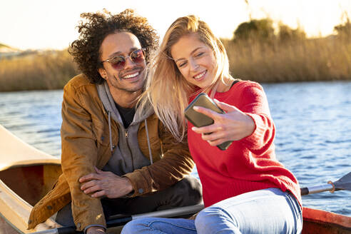 Smiling couple taking selfie through mobile phone while sitting in canoe on river - SBOF02695