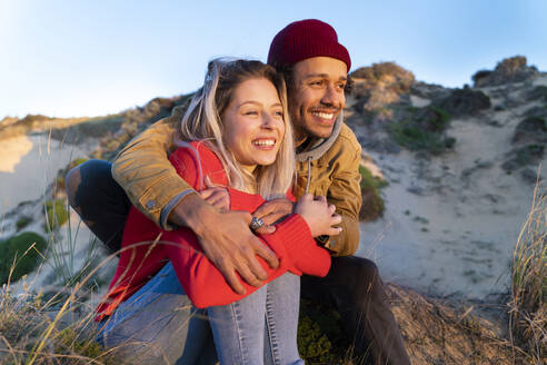 Man wearing knit hat embracing beautiful woman while sitting on sand dune - SBOF02698