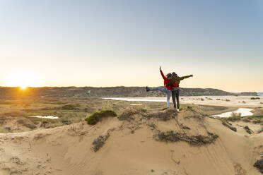 Young carefree couple with hand raised standing by man on sand dune during sunset - SBOF02704