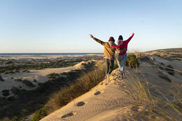Couple with arm around running together on sand dune during sunset - SBOF02707