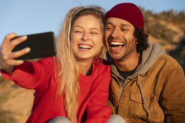 Happy couple smiling while taking selfie through mobile phone sitting outdoors - SBOF02713