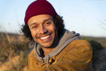 Young man wearing knit hat smiling while sitting outdoors - SBOF02716