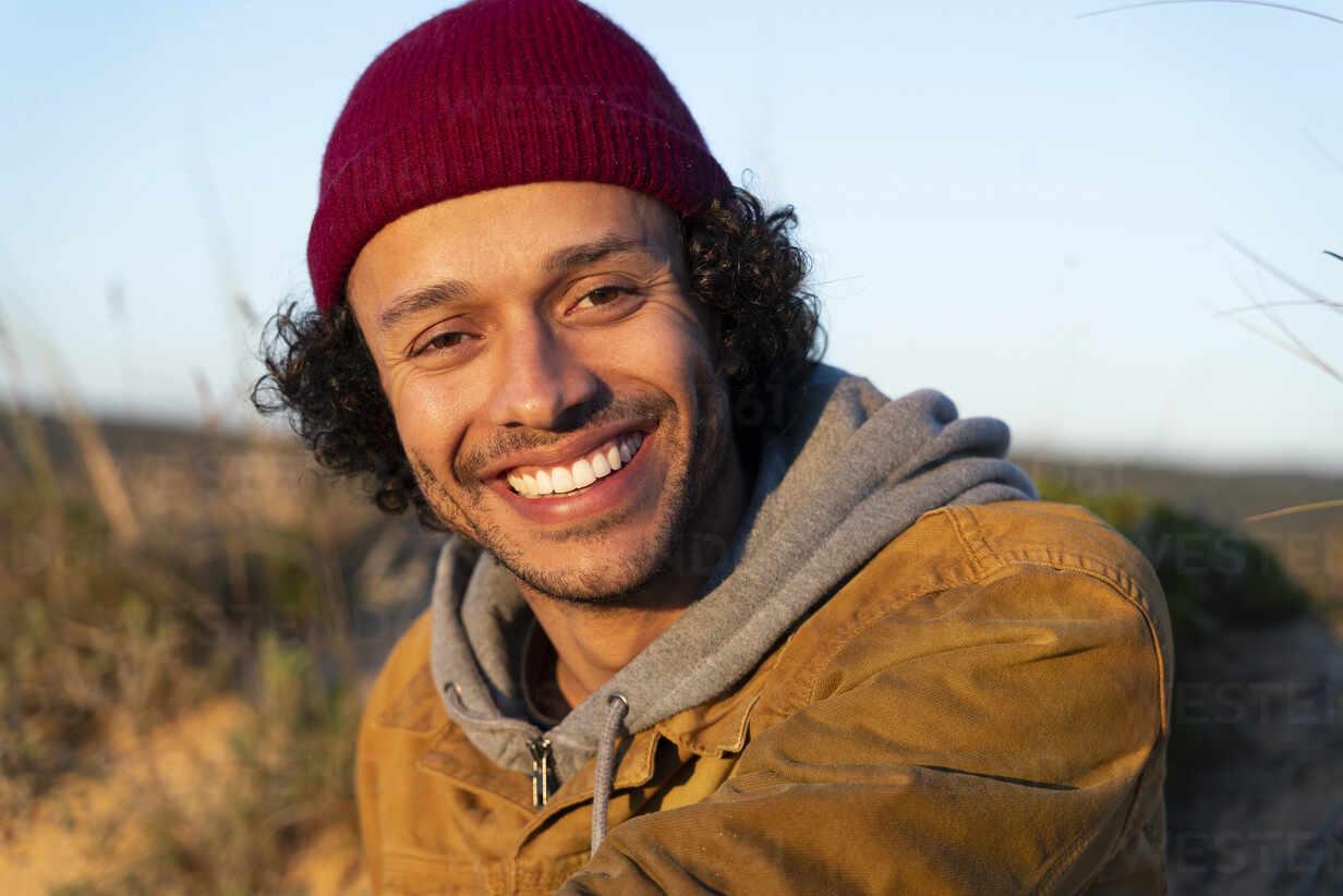 Junger Mann mit Strickmütze, der lächelnd im Freien sitzt - SBOF02716 - Steve Brookland/Westend61