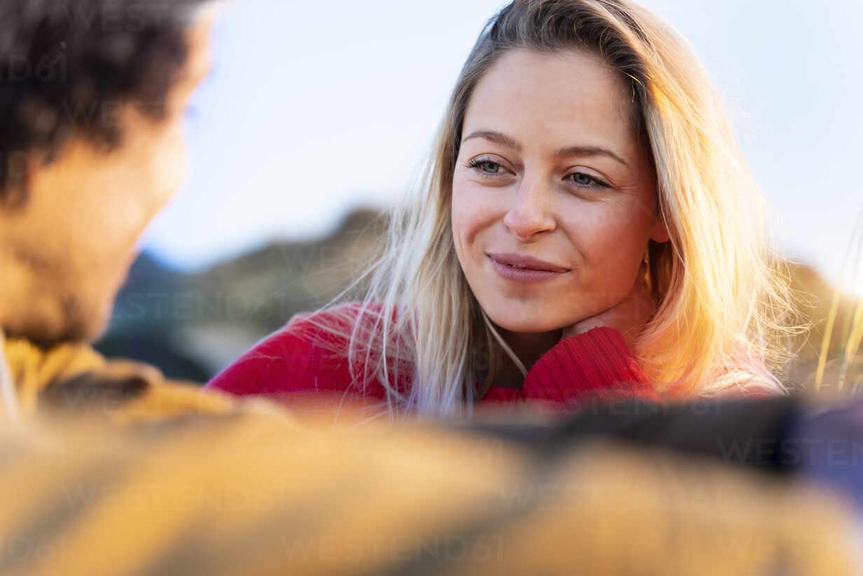 Lächelnde Frau schaut Mann an, während sie im Freien sitzt - SBOF02719 - Steve Brookland/Westend61