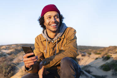 Man with mobile phone looking away while sitting against sky - SBOF02722