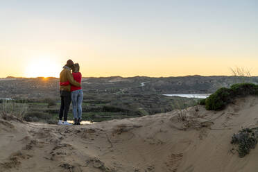 Young couple looking at sunset view while standing on sand dune - SBOF02725