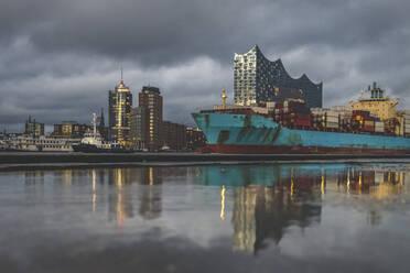 Deutschland, Hamburg, Anleger Theater im Hafen. Hamburger Skyline mit der Elbphilharmonie und ein Containerschiff spiegeln sich in einer Pfütze - KEBF01812