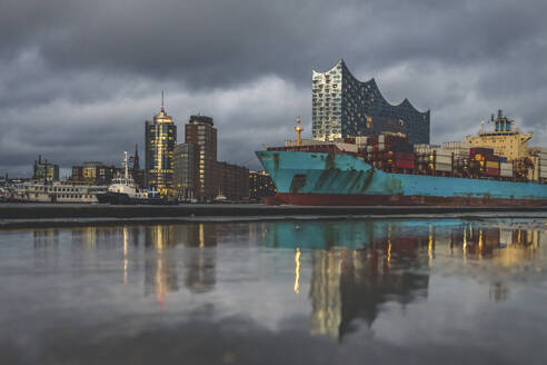 Germany, Hamburg, Anleger theatre, Elbe Philharmonic Hall and container ship reflecting in water - KEBF01812