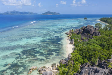 Aerial view of the famous sandy beach Anse Source d´Argent at La Digue Island in distant is Praslin Island. Anse Source d´Argent, La Digue, Praslin, Seychelles, Indian Ocean, Indian Ocean Islands, Africa, Equator. - RUEF03195