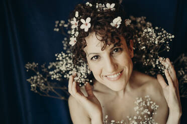 Smiling woman wearing flowers against blue background - GMLF00986