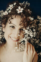 curly hair woman portrait with flowers showing sensity and feminity - GMLF00989