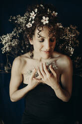 curly hair woman portrait with flowers showing sensity and feminity - GMLF00992