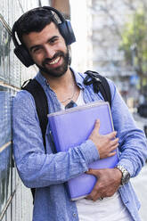 Happy businessman with documents listening music while leaning on wall - PNAF00753