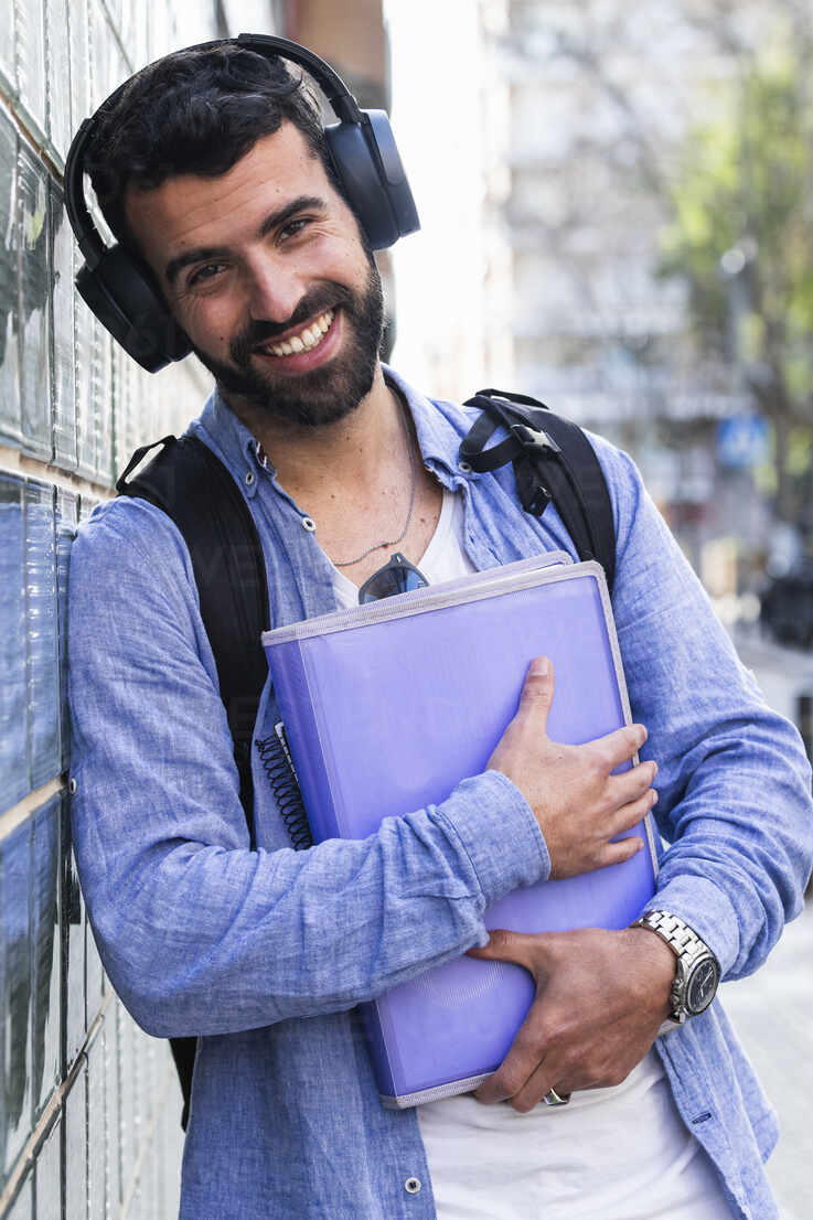 Happy businessman with documents listening music while leaning on wall - PNAF00753 - NOVELLIMAGE/Westend61