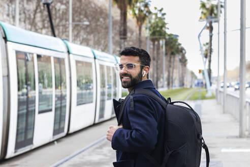 Smiling businessman waiting for train at station - PNAF00759