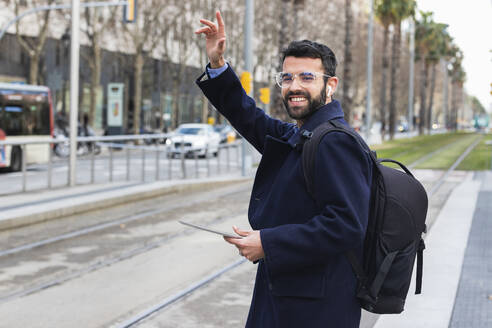 Smiling young businessman with digital tablet waving while standing at station - PNAF00765