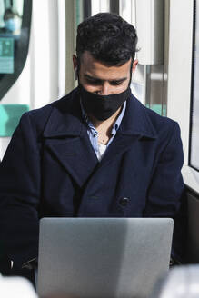 Young businessman wearing protective face mask using laptop while sitting in train - PNAF00771