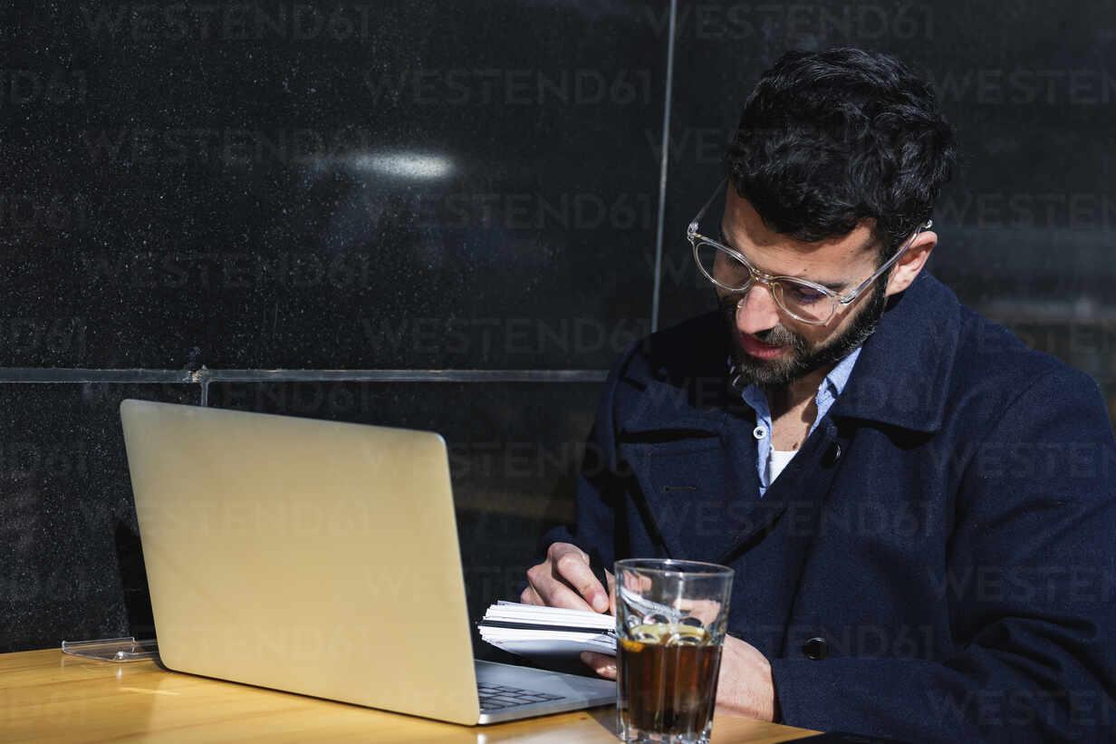 Businessman with laptop writing while sitting at sidewalk cafe - PNAF00774 - NOVELLIMAGE/Westend61
