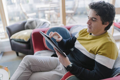 Man using digital tablet while sitting on sofa in living room - BOYF01929