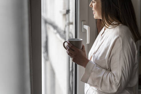 Happy young woman with coffee cup looking through window at home - AFVF08231