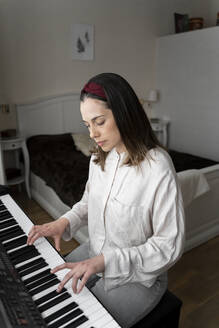 Woman playing piano while sitting in bedroom - AFVF08234