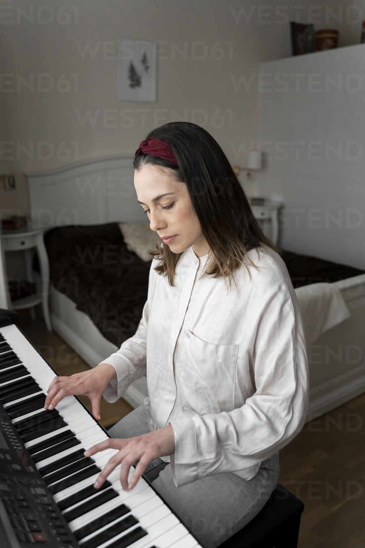Woman playing piano while sitting in bedroom - AFVF08234 - VITTA GALLERY/Westend61