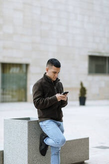 Young man using smart phone while standing against building - OCAF00630