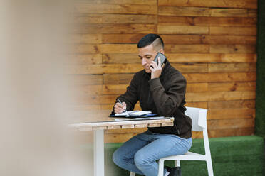 Busy businessman working at cafe while doing a call - OCAF00636
