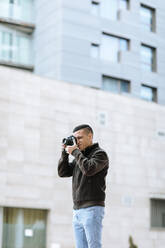 Young male professional photographing through camera while standing against building - OCAF00639