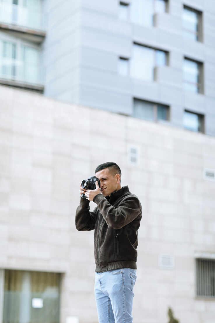 Junger männlicher Profi, der durch die Kamera fotografiert, während er gegen ein Gebäude steht - OCAF00639 - Oriol Castelló Arroyo/Westend61