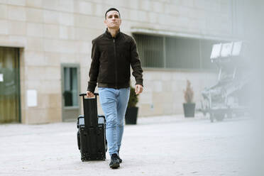 Young boy in blue jeans carrying a suitcase down the street - OCAF00645