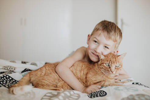 Smiling boy leaning on ginger cat in bedroom at home - GMLF01010