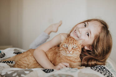 Cute smiling girl with ginger cat on bed at home - GMLF01013