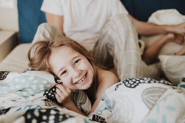 Cheerful girl lying on bed with father sitting in background at home - GMLF01019