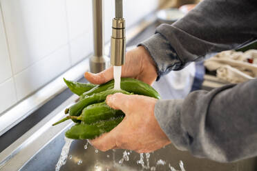 Senior man washing vegetables in kitchen sink at home - AFVF08240