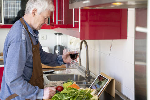 Senior man holding wine glass during video call at kitchen counter in home - AFVF08255