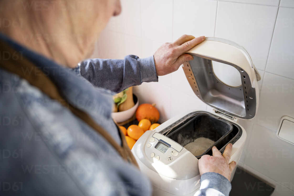 Senior man preparing bread in appliance at home - AFVF08258 - VITTA GALLERY/Westend61