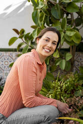 Beautiful smiling woman doing plantation in garden - AFVF08264